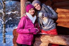 Les amies heureuses passent des vacances d'hiver au cottage de montagne Photographie stock