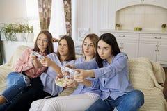 Les amies jouent des jeux vidéo sur le divan dans la chambre Photographie stock libre de droits