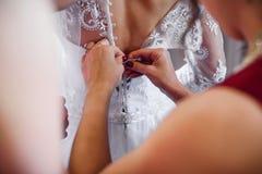 Les amies lacent la robe blanche la jeune mariée dessus de retour sur le corset le jour du mariage Images libres de droits