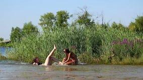Les amies ont l'amusement et étreindre sur la plage de rivière banque de vidéos