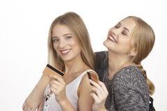 Les amies parlent de dépenser l'argent par la carte de crédit d'or Images libres de droits