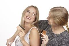 Les amies parlent de dépenser l'argent par la carte de crédit d'or Photo stock