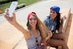 Les amies prenant une photo de selfie sur le patin se garent Photo stock