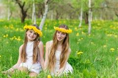 Les amies s'asseyent dans l'herbe avec des guirlandes des pissenlits Photographie stock