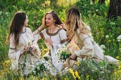 Les amies tissent une guirlande des fleurs sauvages Photos stock