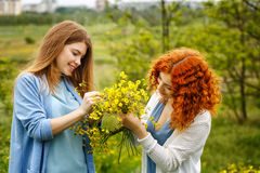 Les amies tissent une guirlande des wildflowers Photo stock