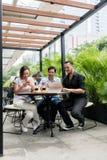 Les amis à l'aide des dispositifs se sont reliés à l'Internet sans fil d'un café moderne Images libres de droits