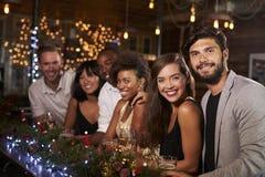 Les amis à la barre pendant une fête de Noël regardent à l'appareil-photo Images libres de droits