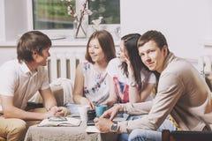 Les amis à la maison et communiquent par l'intermédiaire du processus de boire du thé Photographie stock