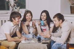 Les amis à la maison et communiquent par l'intermédiaire du processus de boire du thé Image libre de droits