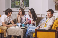 Les amis à la maison et communiquent par l'intermédiaire du processus de boire du thé Images libres de droits
