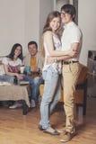 Les amis à la maison et communiquent par l'intermédiaire du processus de boire du thé Image stock