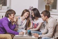 Les amis à la maison et communiquent par l'intermédiaire du processus de boire du thé Photos stock