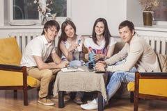 Les amis à la maison et communiquent par l'intermédiaire du processus de boire du thé Photos libres de droits