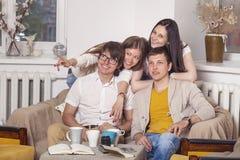 Les amis à la maison et communiquent par l'intermédiaire du processus de boire du thé Photo libre de droits