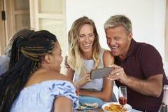 Les amis à une table de dîner regardent des photos sur un smartphone Photographie stock