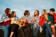 Les amis écoutent des loisirs d'art de jeu de musicien de musicien de rue photos libres de droits