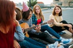 Les amis écoutent des loisirs d'art de jeu de musicien de musicien de rue images stock