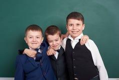 Les amis élémentaires d'écolier, dupant autour près du fond vide de tableau, se sont habillés dans le costume noir classique, élè Image stock