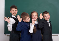 Les amis élémentaires d'écolier, dupant autour près du fond vide de tableau, se sont habillés dans le costume noir classique, élè Photographie stock libre de droits