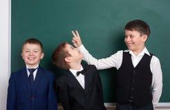Les amis élémentaires d'écolier, dupant autour près du fond vide de tableau, se sont habillés dans le costume noir classique, élè Images stock