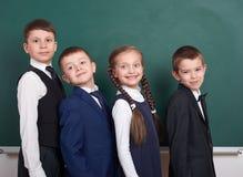 Les amis élémentaires d'écolier, dupant autour près du fond vide de tableau, se sont habillés dans le costume noir classique, élè Image libre de droits