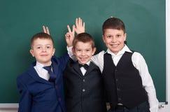 Les amis élémentaires d'écolier, dupant autour près du fond vide de tableau, se sont habillés dans le costume noir classique, élè Photo libre de droits
