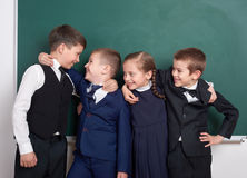 Les amis élémentaires d'écolier, dupant autour près du fond vide de tableau, se sont habillés dans le costume noir classique, élè Images libres de droits