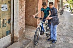Les amis éprouvent la nouvelle bicyclette sur la rue de ville, Kashan, Iran Images libres de droits