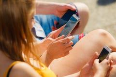 Les amis équipent et des femmes à l'aide des téléphones portables Photo stock