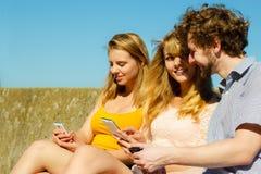Les amis équipent et des femmes à l'aide des téléphones portables Photo libre de droits