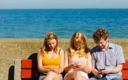 Les amis équipent et des femmes à l'aide des téléphones portables Photographie stock libre de droits