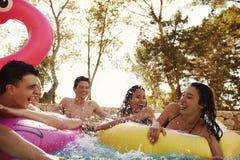 Les amis adolescents ont l'amusement avec des inflatables dans une piscine Image libre de droits