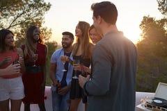 Les amis adultes à une partie sur un dessus de toit au coucher du soleil, se ferment  Image stock