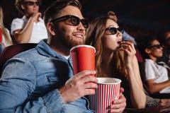 Les amis affectueux de couples s'asseyant dans le cinéma observent le film Image stock