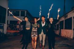 Les amis appréciant la nuit font la fête avec des cierges magiques dans la ville Photo libre de droits