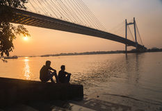 Les amis apprécient la vue de coucher du soleil sur la rivière Hooghly, Kolkata Image stock