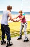 Les amis apprennent que faisant du roller ensemble ayez l'amusement au parc Photo stock