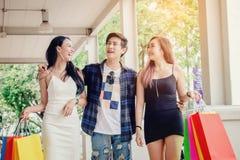 Les amis asiatiques de achat sont marchants et faisants des emplettes dans le stre d'achats Photo stock