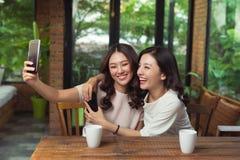 Les amis asiatiques de femme étreignant et font la photo de selfie ensemble Photo stock