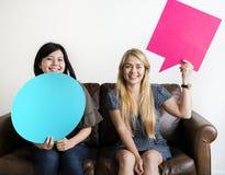 Les amis asiatiques et caucasiens heureux de femmes tenant la parole de copyspace bouillonnent Image stock