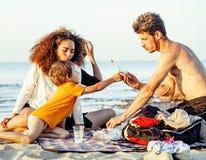 Les amis assez divers de nation et d'âge sur la côte ayant l'amusement, concept de personnes de mode de vie des vacances de plage Photos stock