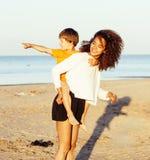 Les amis assez divers de nation et d'âge sur la côte ayant l'amusement, concept de personnes de mode de vie des vacances de plage Image stock