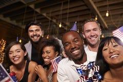 Les amis avec des drapeaux des USA au 4 juillet font la fête dans une barre, se ferment  Image libre de droits