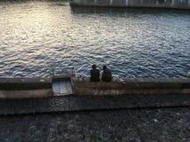 Les amis avec des planches à roulettes s'asseyent par la Seine une soirée d'hiver à Paris Photos stock