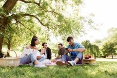 Les amis avec des smartphones sur le pique-nique à l'été se garent Photographie stock libre de droits