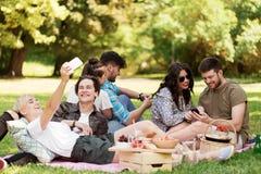 Les amis avec des smartphones sur le pique-nique à l'été se garent Photos libres de droits
