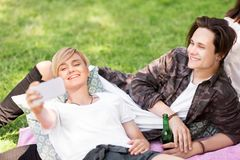 Les amis avec des smartphones sur le pique-nique à l'été se garent Image stock