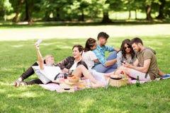 Les amis avec des smartphones sur le pique-nique à l'été se garent Photos stock