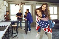 Les amis avec les drapeaux américains rient à l'intérieur Photo stock